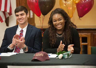 photo by Sarah A. Miller/Tyler Morning Telegraph  Bishop Thomas K. Gorman Regional Catholic School student athletes Connor Hobbs, left, and Kianna Udenze, right, applaud during their signing ceremony at the library Tuesday Feb. 10, 2015.