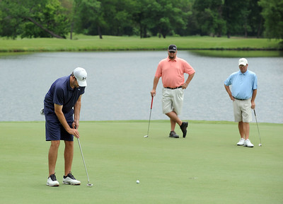 photo by Sarah A. Miller/Tyler Morning Telegraph  Ryan Slaughter putts on the fourth green Friday during round one of the 31st Annual Azalea Invitational at Hollytree Country Club. Also pictured are Les Ledingham, center, and Mike Schrade, right.