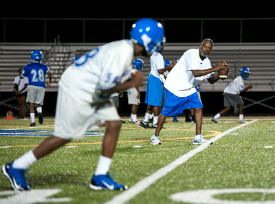 photo by Sarah A. Miller/Tyler Morning Telegraph  John Tyler High School receivers coach Michael Johnson runs through a drill with football players during the team's first day of 5 a.m. practice Monday at the school.