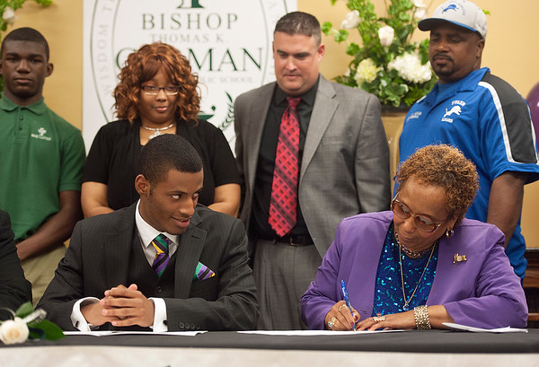 photo by Sarah A. Miller/Tyler Morning Telegraph  Bishop Thomas K. Gorman Regional Catholic School football player Devonte Milton, left, watches as his mother Charlene Milton signs his letter of intent during the NCAA National Signing Ceremony at their school Tuesday. Milton will attend Arkansas Baptist College.