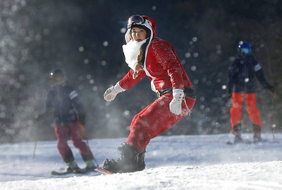 a-snowboarder-right-gets-a-jump-start-as-160-santas-head-down-a-slope-at-sunday-river-during-the-ski-resorts-18th-annual-santa-sunday-event-sunday-dec-3-2017-in-newry-maine-the-santas-raised