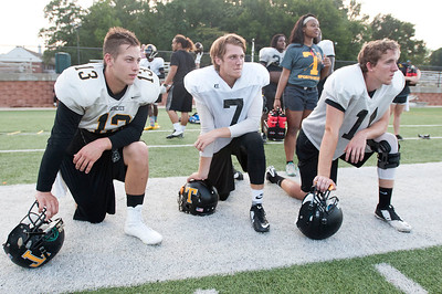 Tyler Junior College football players Erik Richards, Connor Heath and Carter McCown kneel as they watch their teammates run a drill Tuesday evening at Pat Hartley Field.  (Sarah A. Miller/Tyler Morning Telegraph)