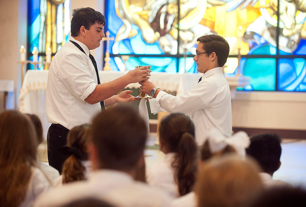 Robbie Chiasson receives communion from fellow football player quarterback Michael Goodwin during a special mass service with football players from Bishop T.K. Gorman and visiting team St. Bernard's Academy Wednesday Aug. 26, 2015. Goodwin was made an extraordinary minister to help serve communion during large school mass services.   (Sarah A. Miller/Tyler Morning Telegraph)